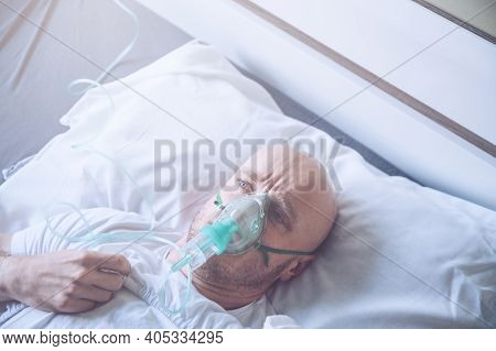 Sick Man With Breathing Problem With Oxygen Mask Or Ventilato