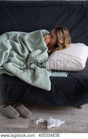 Sick Woman At Home Lying In Bed Suffering From Allergy, Flu Symptom, Covering With Plaid And Blowing