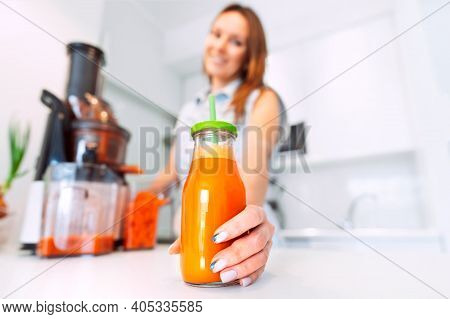 Happy Healthy Woman Making Fresh Carrot Juice In A Juicer In The Kitchen At Home. Bottle Of Fresh Ho