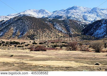 Rural Grasslands And A Riparian Woodland Surrounded By Snow Covered Mountains Taken On Arid Badlands