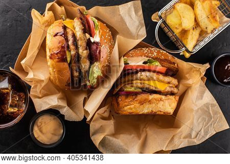 Two yummy grilled chicken burgers in a craft box, fries and cola on a dark background, top view. Hamburger and French fries. Fast food set to take away.