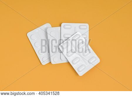 Packets Of Medication In A Pile On An Orange Background, Stack Of Blister Packs