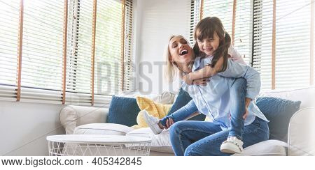 Happy Beautiful Mother Carrying Or Piggyback Her Little Daughter Laughing Playing And Having Fun Tog