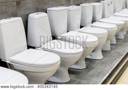Diagonal Row Of Modern New White Toilet Bowls In A Plumbing Store. Selected Focus