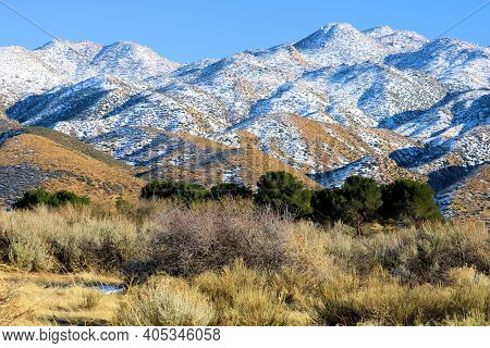 Snow Covered Mountains Besides An Arid Field With Sage Plants Taken On Rural Windswept Badlands In T