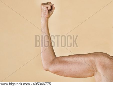 Woman flexing her muscles as a concept for feminism on a yellow background