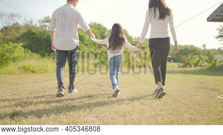 Happy Young Asian Family Walking On Path Holding Hands His Little Girl, They Are Walk In The Park An