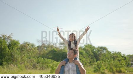 Happy Young Asian Father Piggyback With His Little Girl, She Play The Toy Airplane And Have Enjoyed