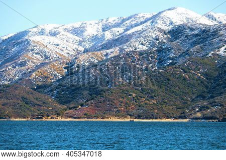 Barren Mountains Covered With Snow Surrounded By Silverwood Lake, Ca Taken In The Rural Mojave Deser