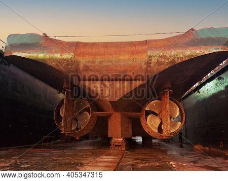 Industry View - Ocean Vessel In The Dry Dock In Shipyard. Old Rusty Ship Under Repair