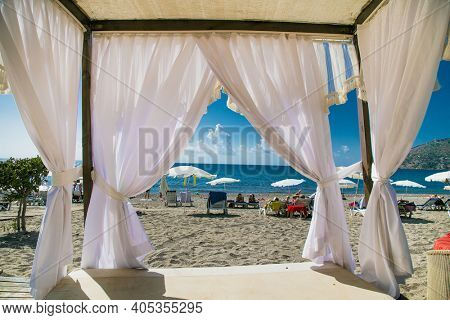 Alanya, Turkey -October 20, 2020: Luxury wood framed whit  curtains for relaxing on the sandy beach in Alanya,  Turkey.