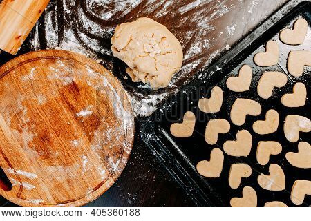 Cookies In Shape Of Heart For The Saint Valentines Day. Man Is Baking Heart Shape Cookies For Saint