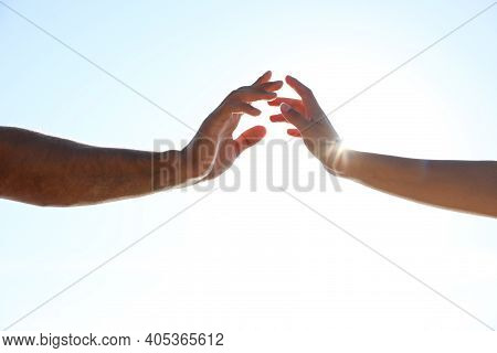 Man And Woman Reaching Hands To Each Other Against Blue Sky, Closeup. Nature Healing Power