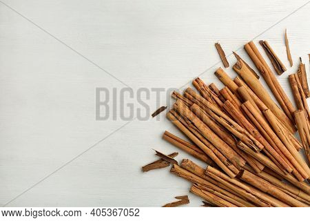 Aromatic Cinnamon Sticks On White Wooden Table, Flat Lay. Space For Text