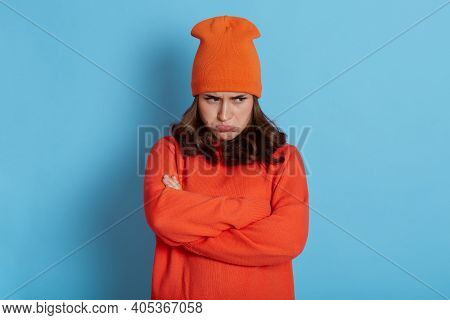 Dark Haired Caucasian Woman Stands With Arms Folded Over Body, Looks From Under Forehead With Pout L