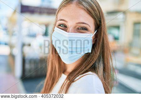 Young caucasian woman wearing coronavirus protection medical mask walking at the city