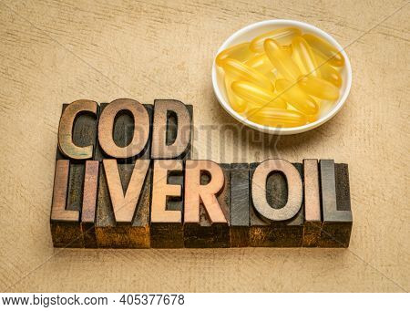cod liver oil - dietary supplement, a bowl of capsules with vintage letterpress wood type text, healthy eating concept