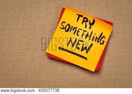 Try something new advice or reminder - handwriting on a sticky note, business, education or personal development concept