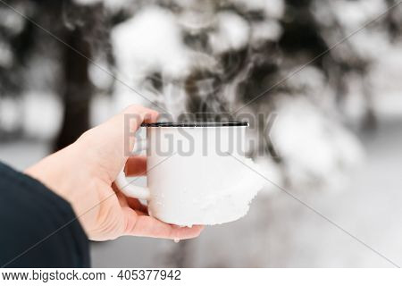 Hot Drink In Cold Weather. Hand Holding Steel Mug With Hot Drink Outdoors, Close-up. Steam Rising Fr