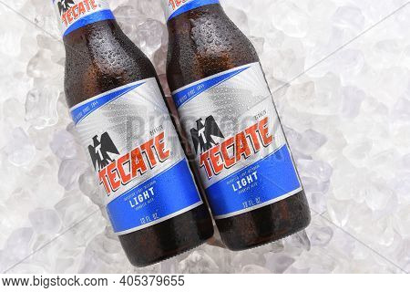IRVINE, CA - JUNE 14, 2017: Tecate Light bottles on Ice.  Two bottles of Tecate Light, a popular pale lager named after the city of Tecate, Baja California, where it was first produced in 1943.