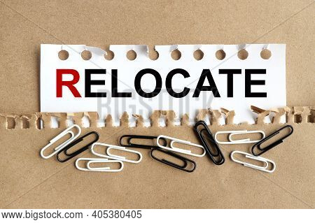 Relocate, Text On White Paper On Torn Background