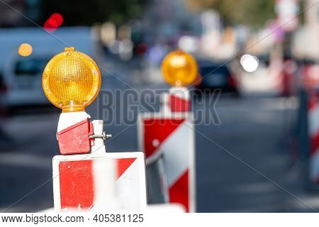 Warning Poles With Orange Light Signal On The Road About Repairs Work, Blurred Street With Cars On B