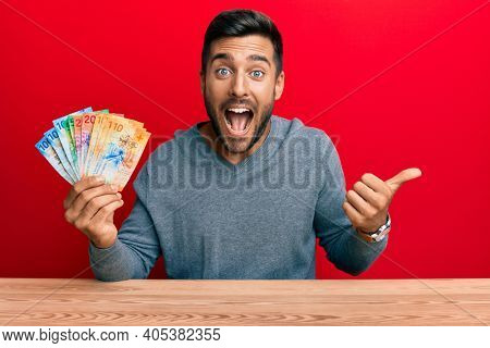 Handsome hispanic man holding swiss franc banknotes pointing thumb up to the side smiling happy with open mouth