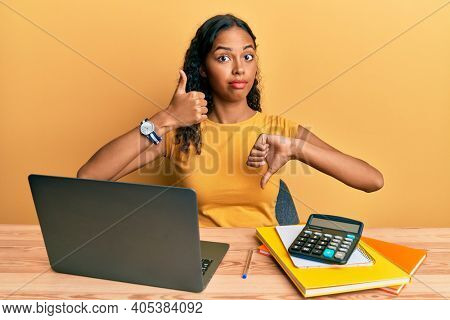 Young african american girl working at the office with laptop and calculator doing thumbs up and down, disagreement and agreement expression. crazy conflict