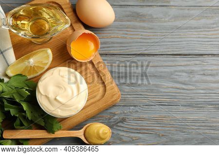 Board With Bowl Of Mayonnaise And Ingredients For Cooking On Wooden Background