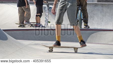 Lower Body Parts Of Boys With Skateboards And Bmx Bike In Concrete Skate Park