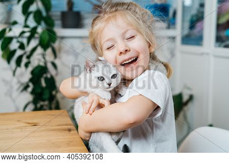 Child Playing With Little Cat. A Little Girl Holds A White Kitten. A Little Girl Snuggles Up To A Cu