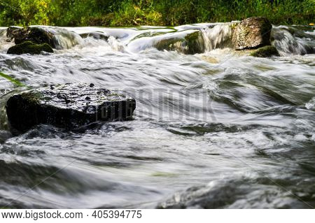 River Flow Over Rocks In Summer Day. Waves Of The River Flow. Relaxing Nature Landscape Scenics