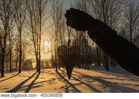 Womans Hand Holding A Wooden Heart On Winter Snowy Forest Evening Background. Love Winter Or St. Val