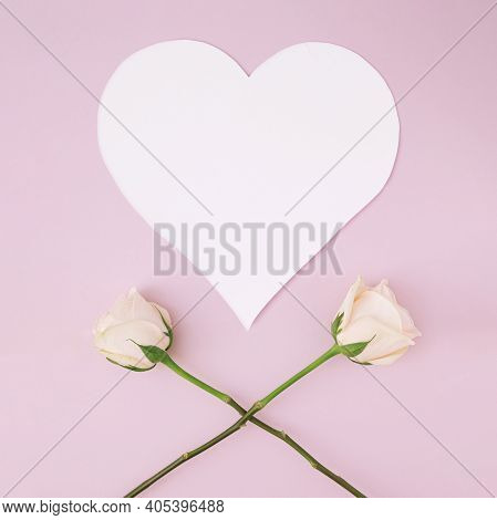 White Heart Shape Greeting Card Idea With Two Long Stem Roses Crossed To Make X Shape On Pastel Pink