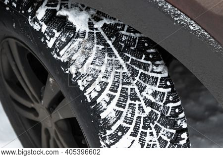 Dirty Suv Car Wheel. Snow Tire With Metal Studs, Which Improve Traction On Icy Surfaces, Close Up Ph