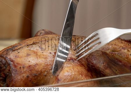 On The Dining Table, A Piece Of Meat Is Cut From A Roast Duck With A Knife And Fork, Close-up, Selec
