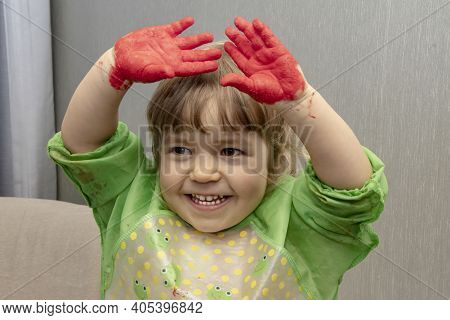 A Little Girl Holds Her Hands Above Her Head, Which Are Smeared With Children's Hand Paints. Concept