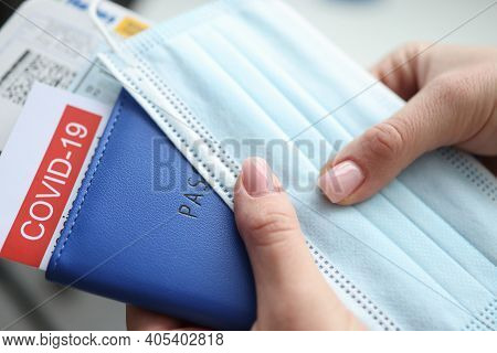 Female Hand Holding Covid-19 Vaccination Passport And Plane Tickets Closeup. Traveling Abroad During
