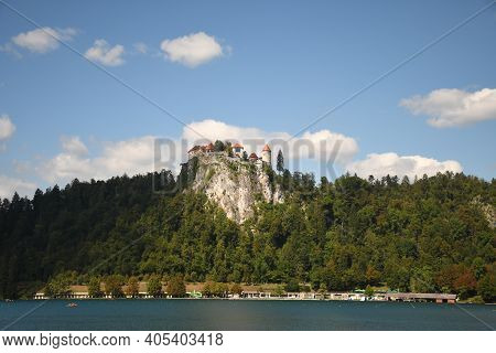 Summer View Of Bled Lake And Bled Castle On A Rock Among Green Forest.