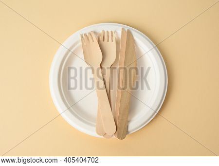 Wooden Fork And Empty White Round Brown Disposable Plate Made From Recycled Materials On A Brown Bac
