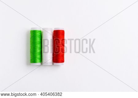 Three Spools Of Thread For Sewing Are Stacked In The Form Of The Flag Of Italy On A White Background