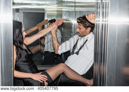 Young Man Holding Hand Of Passionate Woman While Seducing Her In Elevator.