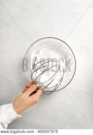 Young Womans Hand Holding Whisk Over The Bowl Of Whipped Cream. White Kitchen Background. Food And H