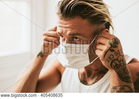 Artsy man putting on a face mask due to pollution
