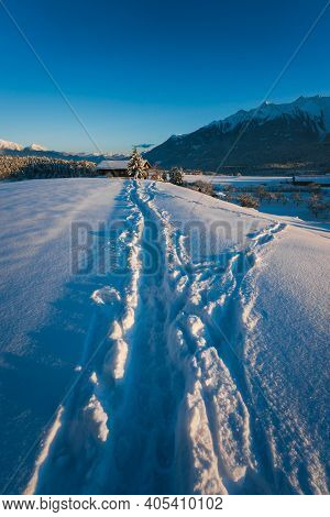 Long Deep Eep Snow Trail Path To Traditional Austrian House In Sunlit Alpine Winter Landscape During