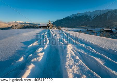 Deep Snow Trail Path In Sunlit Mountain Winter Landscape Towards Typical Austrian House During Sunse