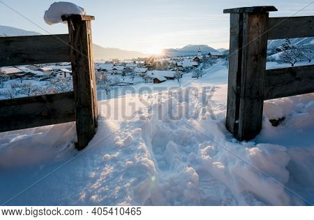 Snow Covered Alpine Traditional Austrian Village In Winter Landscape During Sunset With Sun Star Bet