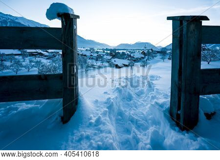 View Through Fence To Alpine Winter Landscape During Blue Hour Dusk With View Over Small Austrian Tr