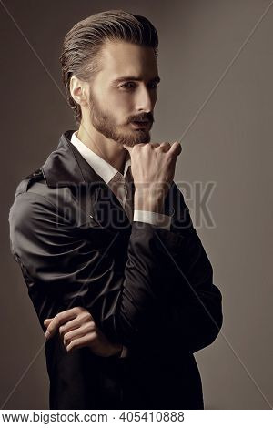 Portrait of a brutal handsome man with dark hair and a beard posing in black coat and white shirt. Men's beauty.