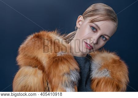 Portrait of a happy cute girl in a fox fur coat on a dark blue background with snow. Winter fur coat fashion.